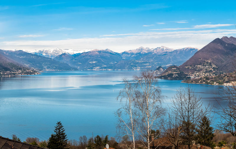Landscape of Lake Maggiore on a clear winter day, Stresa, Piedmont, Italy Mountain Scenics - Nature Water Beauty In Nature Tranquil Scene Sky Cloud - Sky Lake Mountain Range Nature Non-urban Scene Tree Plant No People Idyllic Outdoors Snowcapped Mountain Tranquility Cold Temperature Day Landscape Blue Background Lake Maggiore