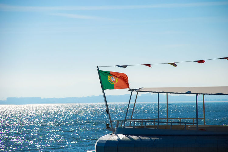 Flag on boat against sea and clear sky