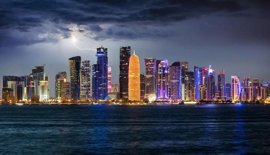 Sea by illuminated buildings against sky at dusk