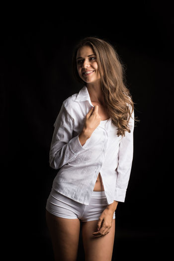 Portrait Looking At Camera Young Adult Studio Shot Beauty Black Background Hair One Person Smiling Women Beautiful Woman Young Women Indoors  Standing Adult Hairstyle Long Hair Front View Three Quarter Length Fashion