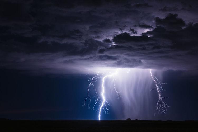 A dramatic lightning bolt illuminates an approaching thunderstorm near holbrook, arizona.