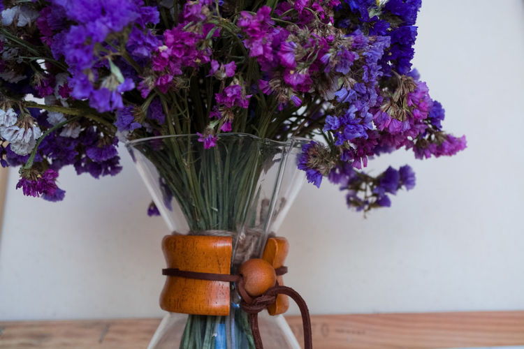 Close-up of purple flower vase on table against wall