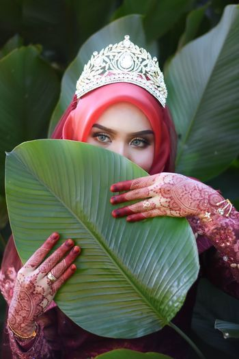 Woman wearing crown holding leaf