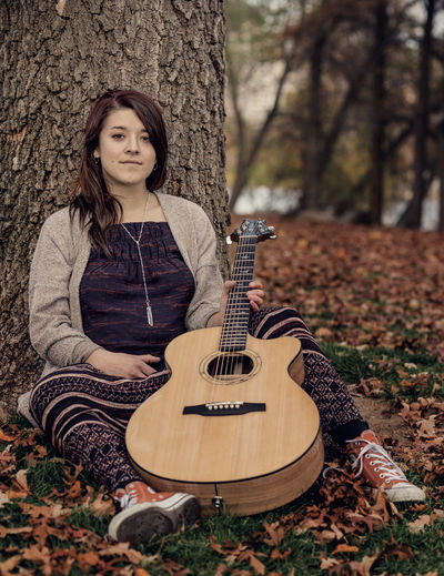 A Girl And Her Guitar Day Fall Colors Full Length Guitar Leaves Musical Instrument One Person Outdoors Portrait Relaxing Sitting Tree Young Adult Young Women
