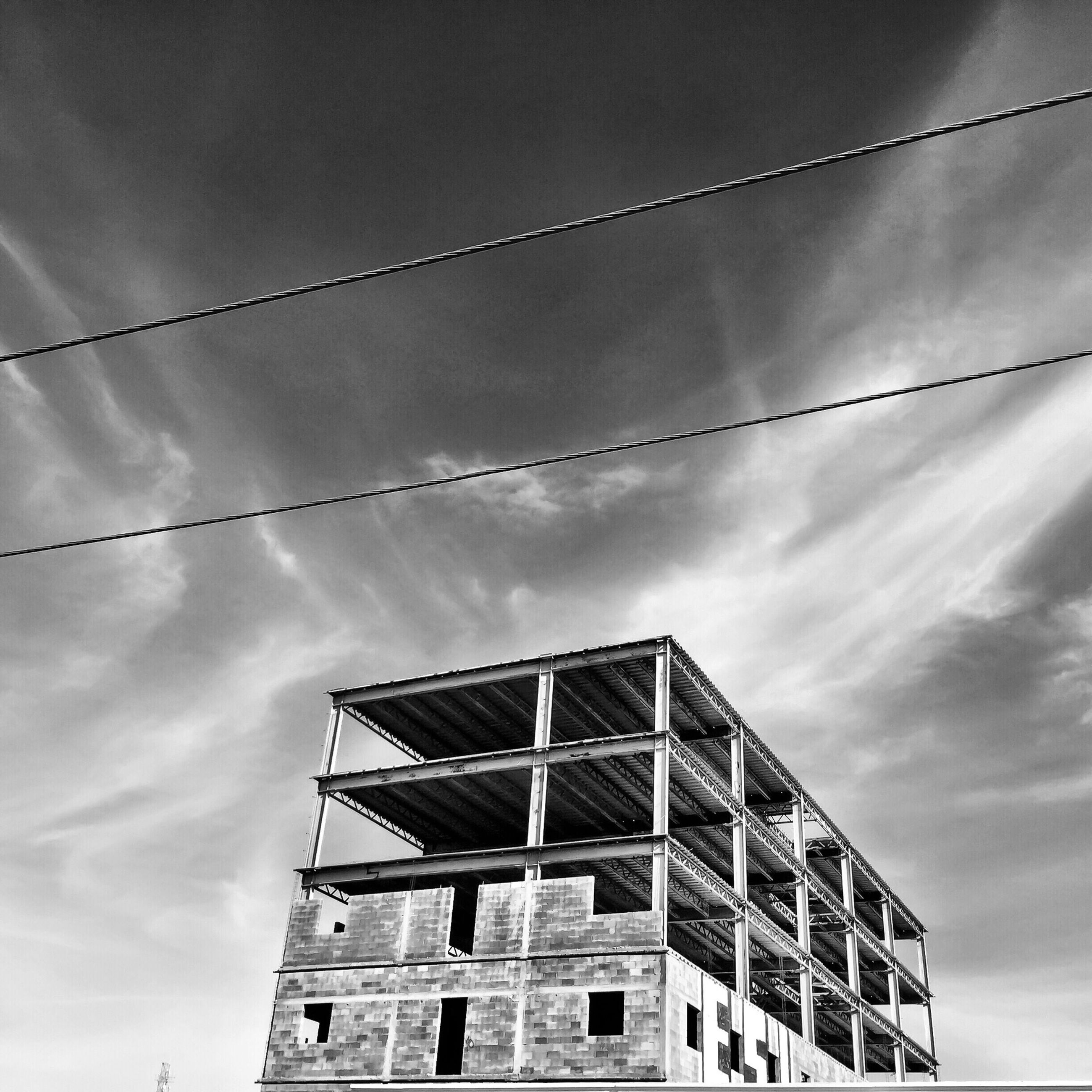 architecture, low angle view, building exterior, built structure, sky, cloud - sky, cloudy, building, cloud, residential structure, residential building, house, outdoors, day, window, no people, high section, cable, city, power line