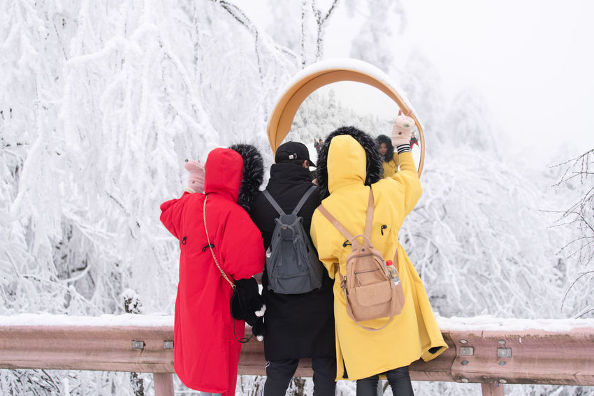 Two ladies and one man in winter clothes taking selfies in front of a mirror at snowy road side. Winter Snow Cold Temperature Clothing Togetherness Women Warm Clothing Rear View Bonding People Real People Leisure Activity Outdoors Yellow Selfie Road Mirror Roadside Coat Winter Clothes Red Black Young Young Adult Outdoor Fun