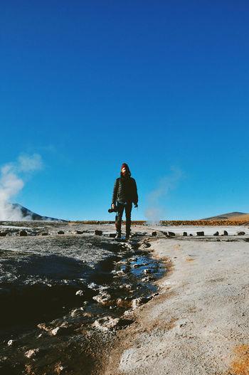 Man standing on desert against clear blue sky