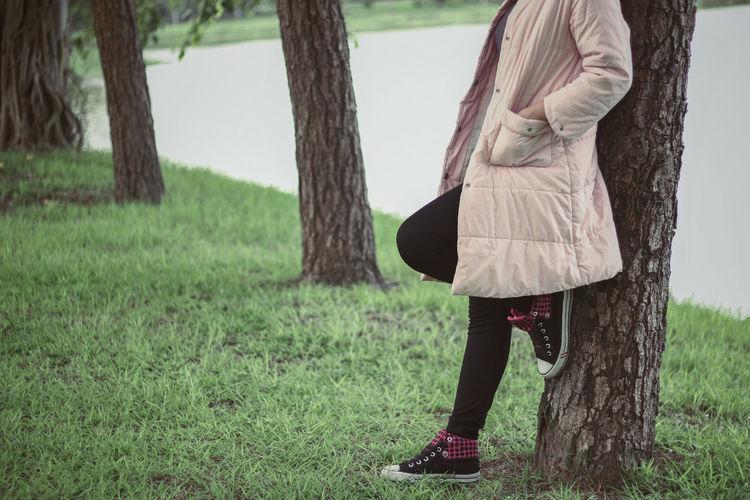 Woman standing by tree trunk in field