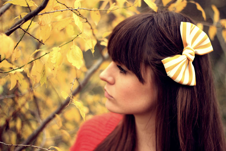 Woman wearing hair bow against tree
