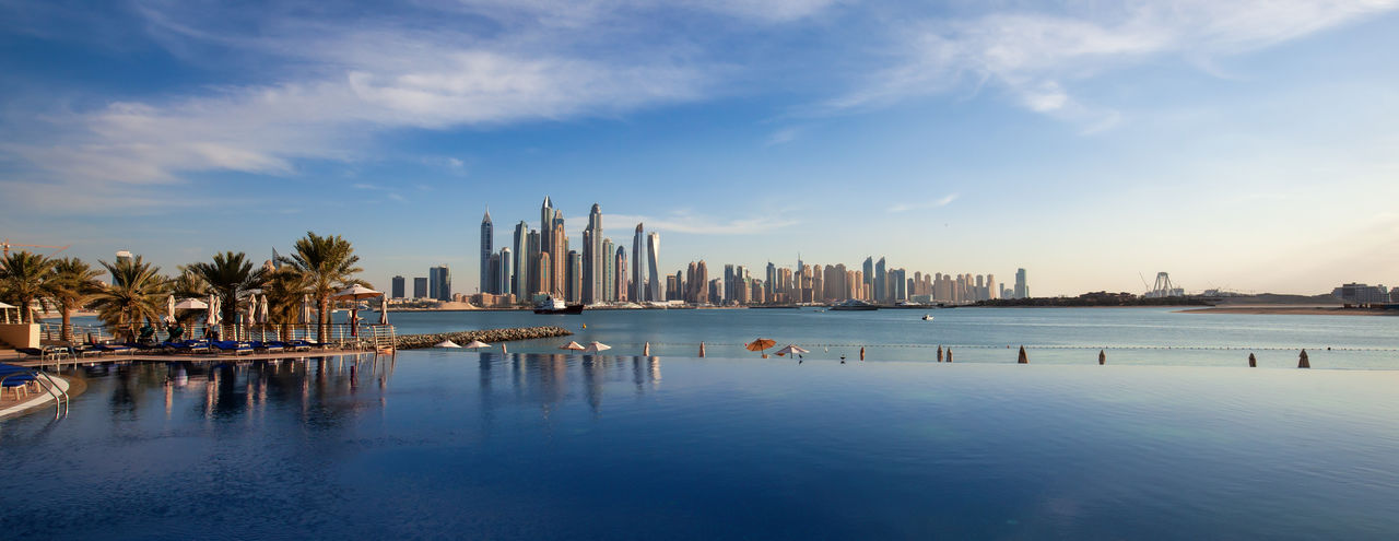 Panorama of Dubai Marina Skyline with a beautiful infinity swimming pool in front. Water Sky Building Exterior Architecture Built Structure Reflection City Waterfront Cloud - Sky Nature Office Building Exterior Skyscraper Beauty In Nature No People Skyline Sunset Travel Travel Destinations Tourism Tourist Reflection Landscape Dubai UAE United Arab Emirates Sea Ocean Resort Hotel Marina Beautiful Urban Modern Desert ASIA Horizon Over Water Futuristic Day Colorful City Cityscape Backgrounds Gulf Infinity Pool Light Panorama Luxury Architecture Beach