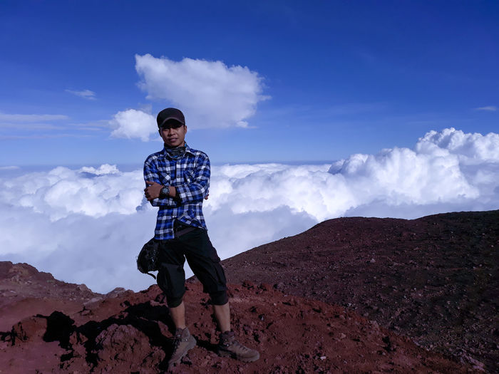 Portrait of young man standing on mountain against sky