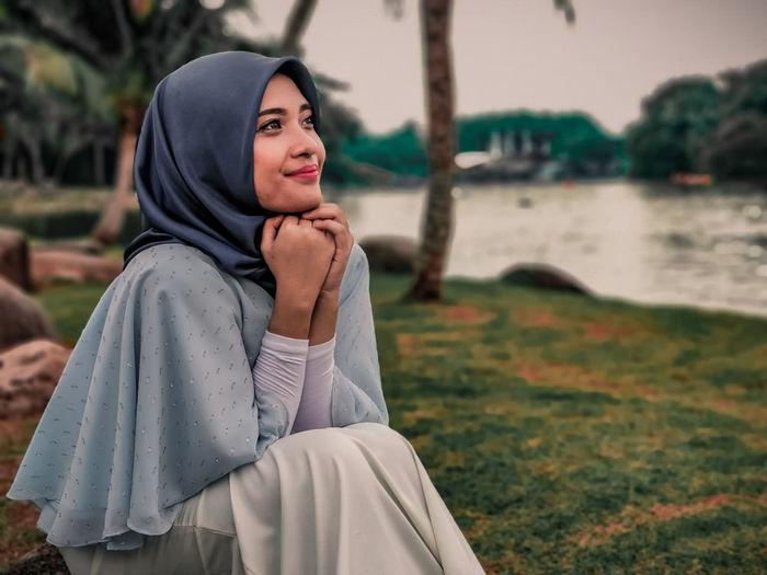 Beautiful young woman sitting by lake