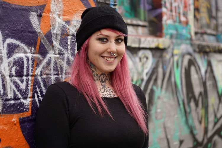 Alternative Authentic Casual Clothing Emo Girl Graffiti Inked Lifestyles Looking At Camera Person Pierced Piercing Pink Hair Portrait Punk Real People Smiling Street Tattoo Tattooed Urban Woman Young Adult Young Women Youth