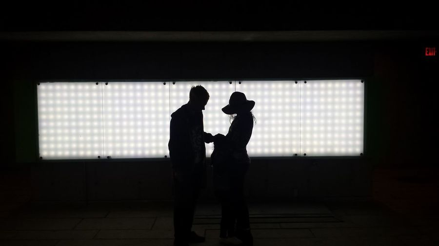 Silhouette couple standing against window