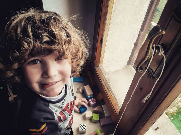 High angle portrait of cute boy playing with blocks on window sill at home
