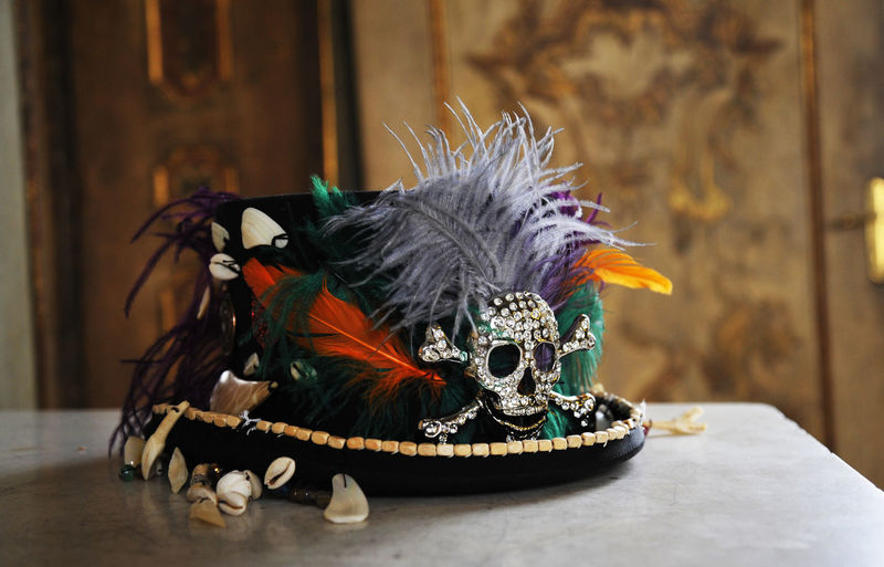 Close-up of feather and skull on hat
