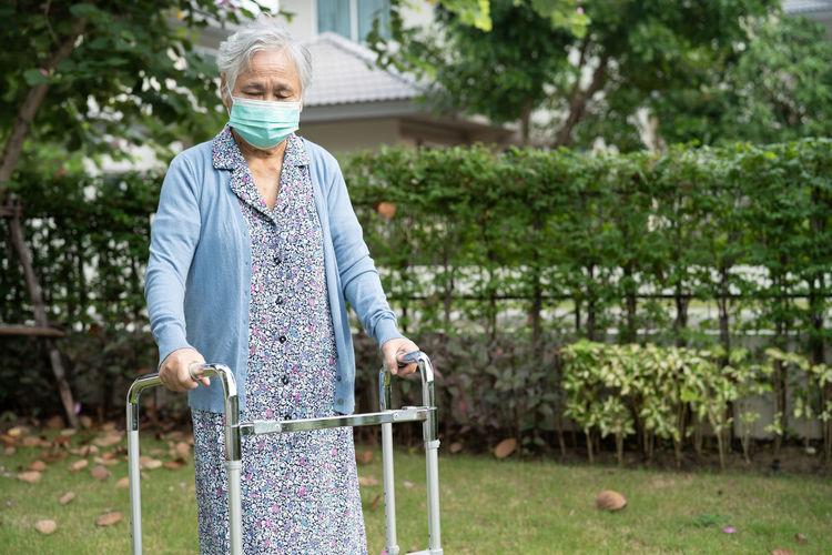 Senior woman wearing mask walking at lawn