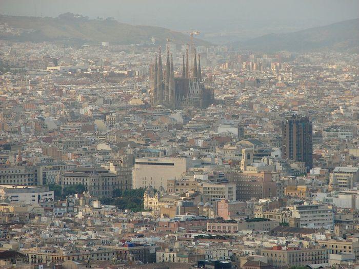 Sagrada Familia Amidst Buildings In City At Dusk