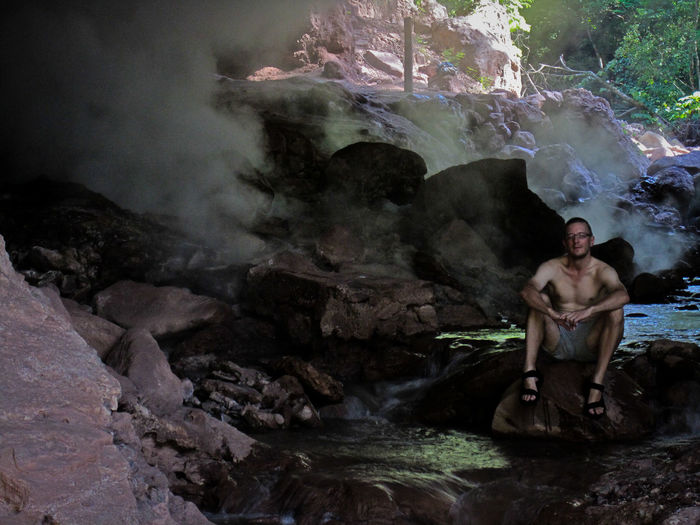 Honduras Aguas Termales De Azacualpa Water Rock One Person Shirtless Real People Solid Rock - Object Nature Young Adult Lifestyles Sitting Rock Formation Leisure Activity Motion Full Length Men Day Looking At Camera Outdoors Flowing Water Flowing Hot Spring Power In Nature