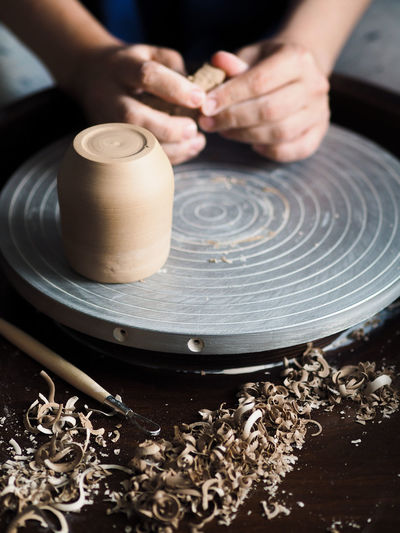 The master removes the excess clay from the workpiece for the future mug with a special tool.