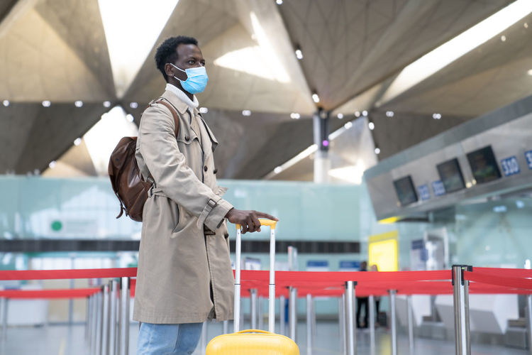 Young businessman wearing mask standing at airport