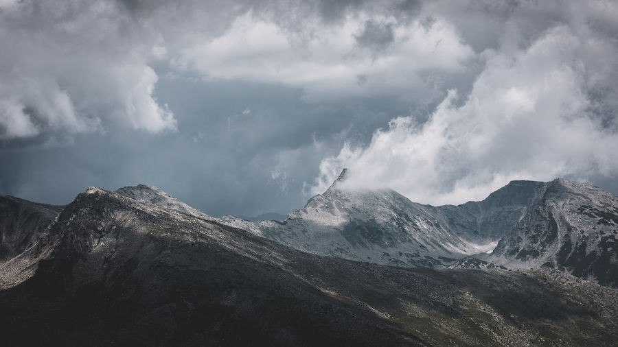 Panoramic view of snowcapped mountains against cloudy sky