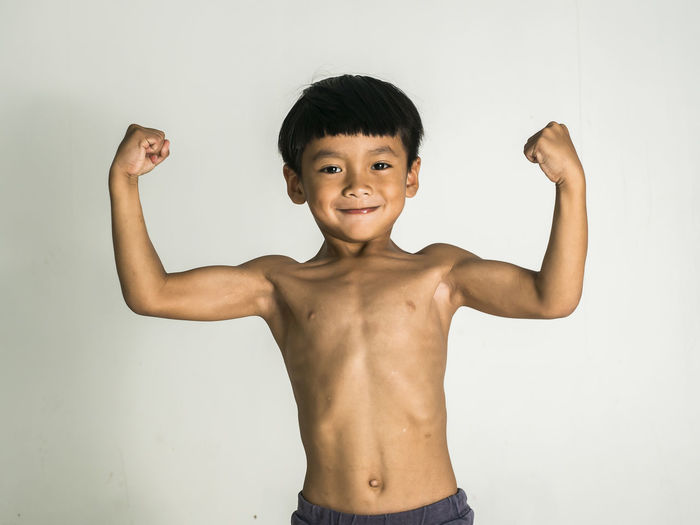 the Boy showing muscle For strong health. The concept of good health Muscular Build Flexing Muscles Childhood Lifestyles Boys Smiling Arms Raised Human Arm Masculinity Portrait Healthy Eating Boy