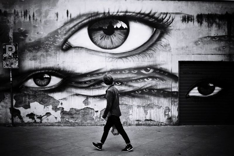 Eyes on you (mono) Streetphotography Monochrome EyeEm Best Shots Black And White Photography Big Brother Surveillance Real People One Person Lifestyles Leisure Activity Full Length Auto Post Production Filter Child Wall - Building Feature Creativity The Street Photographer - 2018 EyeEm Awards