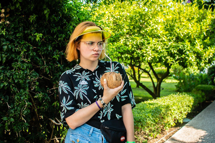 Young woman drinking coconut water with straw while standing in park
