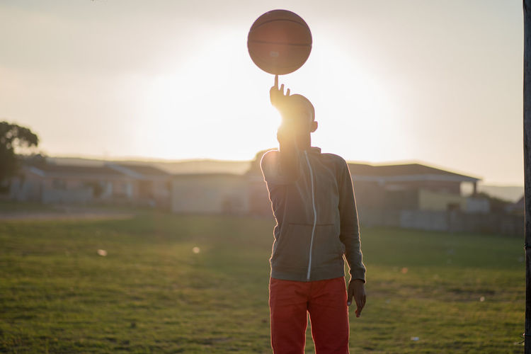 Boy spinning basketball One Person Sky Real People Field Standing Land Leisure Activity Nature Lifestyles Sunset Grass Focus On Foreground Three Quarter Length Sport Sunlight Casual Clothing Men Young Adult Ball Lens Flare Outdoors Basketball Spinning