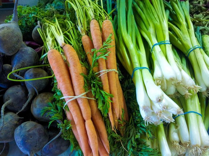 Close-up of spring onions and carrots for sale at market stall