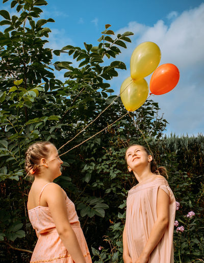 Portrait of a smiling girls with balloons against trees