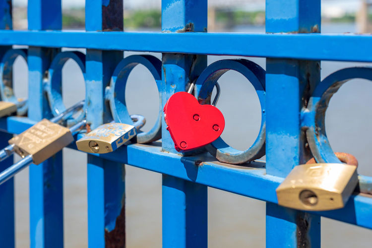 Close-up of padlocks on fence at bridge