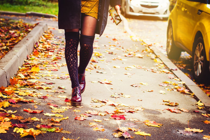 Low section of woman walking on street during autumn