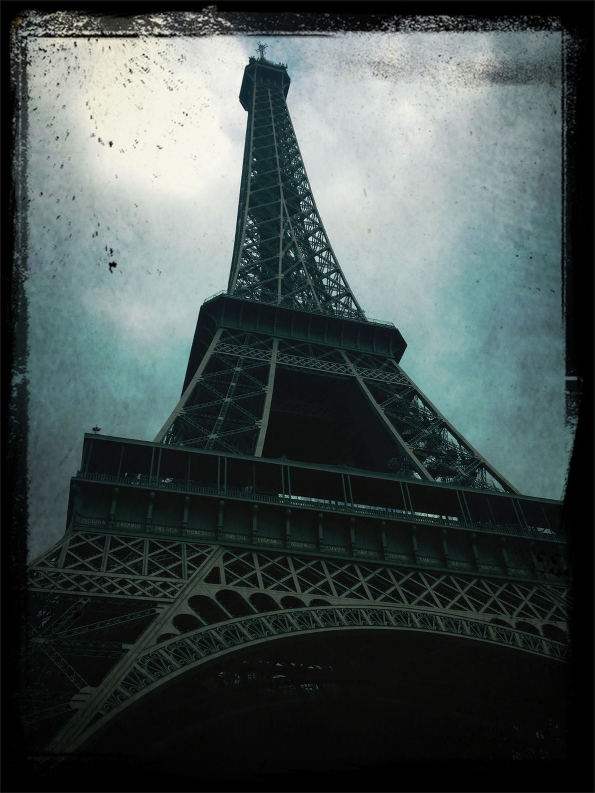eiffel tower, international landmark, architecture, famous place, built structure, culture, travel destinations, low angle view, transfer print, tourism, capital cities, tower, travel, metal, tall - high, history, sky, auto post production filter, architectural feature, metallic