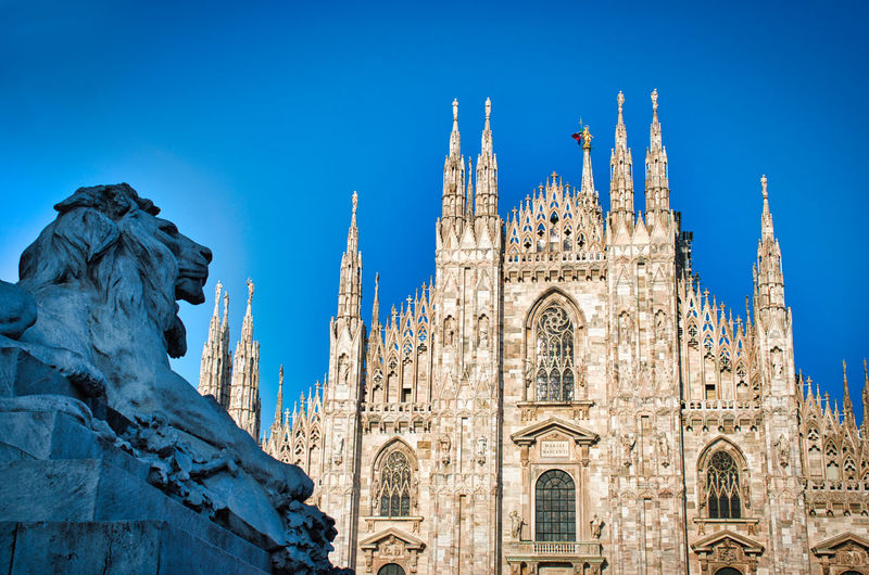 The golden sunshine is reflecting on the front of the magnificent duomo di milano or milan cathedral