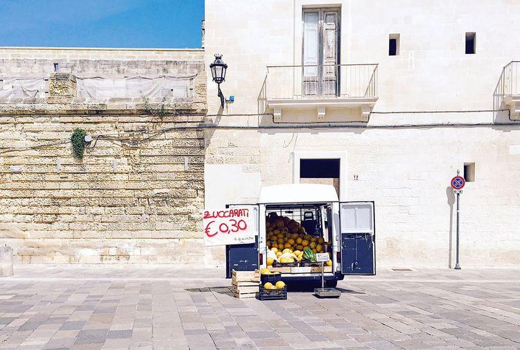 Fruits in van for sale against building