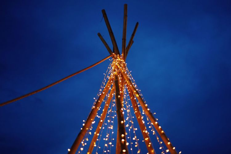 Low angle view of illuminated christmas lights against clear blue sky