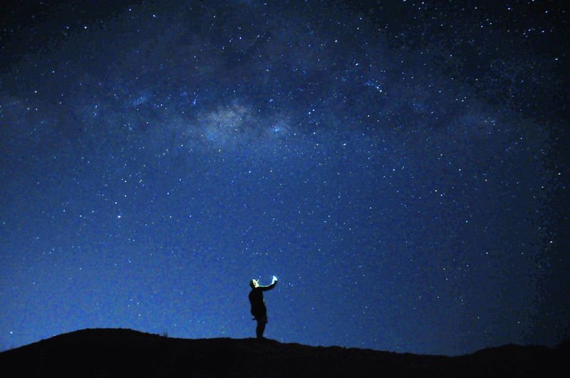 Silhouette man standing on land against sky at night