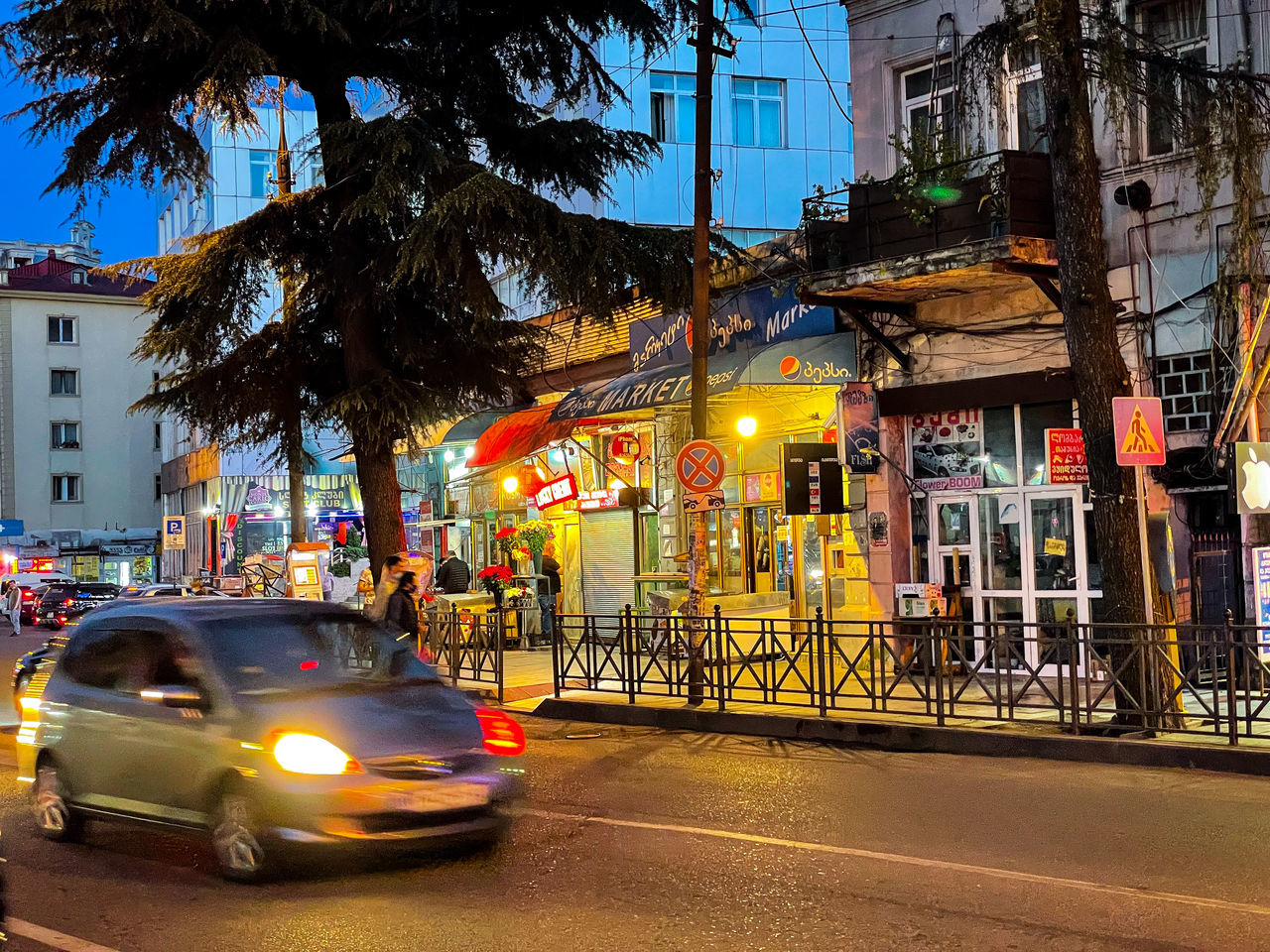 ILLUMINATED CITY STREET BY BUILDING AT NIGHT