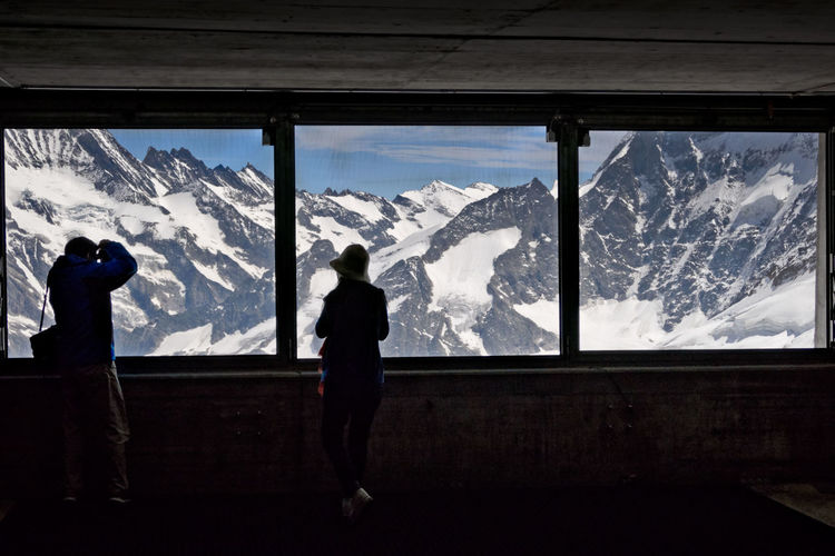 Rear View Of People Looking At Snowcapped Mountains At Observation Point