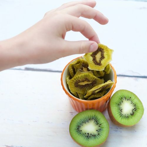 Cropped Hand Of Person Holding Kiwi Slice At Table