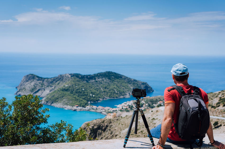 Summer holiday weekend visiting Greece Europe. Male freelance photographer with backpack enjoying capture time lapse of Mediterranean village Assos from top view point platform. Camera on tripod Camera Capture The Moment Coastline Greek Lanscape Photography Man Rear View Relaxing Trip Vacations Weekend Backpack Blue Sky Coast Cruise Enjoying Island Kefalonia Mediteranean Outdoors Photograpghy  Sea Sommer Traveler Tripod Visiting