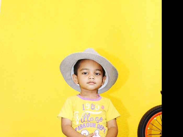 Portrait Of Innocent Boy Wearing Hat Against Yellow Background