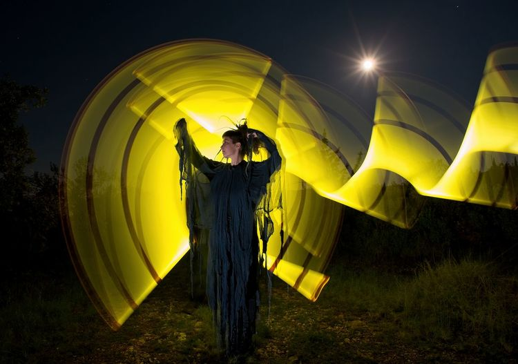 Full length of woman with light painting standing against sky at night