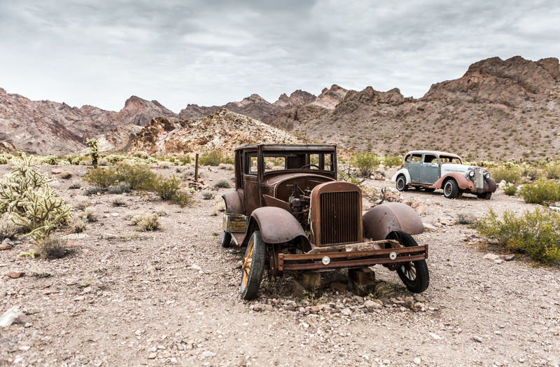 Abandoned truck on field against mountains