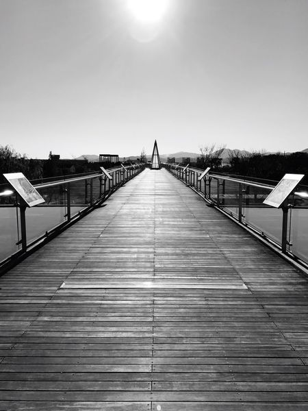 Sunlight The Way Forward Built Structure Outdoors Architecture Day Clear Sky No People Sky Shadow Water Footbridge Building Exterior Nature White Sunlight Black Bridge One Way Black And White Friday EyeEm Black And White Friday AI Now