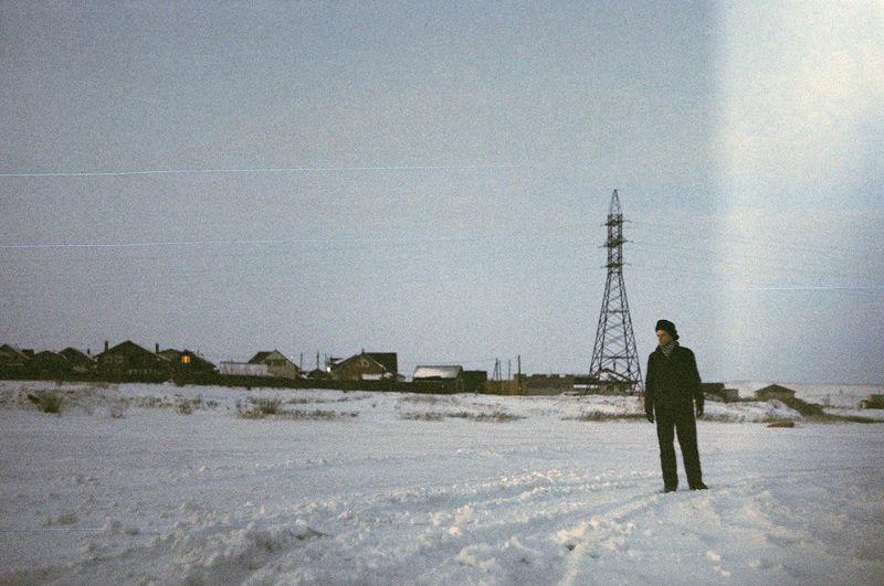 Full length of man standing on field against sky during winter