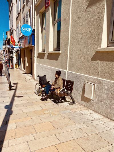 Man sitting on footpath against building