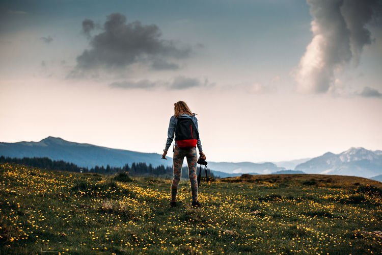 Rear View Of Woman With Backpack Standing On Landscape Against Sky During Sunset